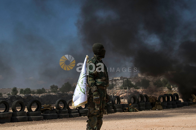 Fighters of Jaysh al-Izza formation of the Syrian armed opposition, take part in a military show during their graduation from a special forces course in Idlib, where medium and heavy weapons were used to prepare them to be sent to the battles of Hama, Syria, July 15, 2019. The course was named after Abdel Basset Al Sarout, a former Syrian goalkeeper and a rebel, who was killed while fighting in the battles of Hama. Photo by Mouneb Taim