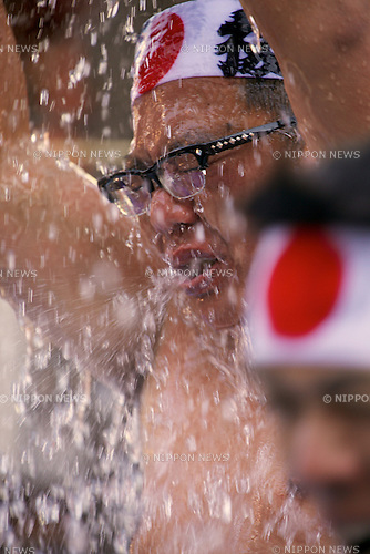 """January 10, 2015, Tokyo, Japan : A participant pours himself cold water during the Annual New Year ice bath ceremony at Kanda Myojin Shinto. A group of 38 brave men a women wearing  only shorts or loincloths pour cold water over themselves in a traditional """"soul-purification"""" ceremony to test their endurance, they believe would purify their souls and bring them good luck.  (Photo by Rodrigo Reyes Marin/AFLO)"""