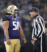 Vita Vea and a referee share a laugh between plays.