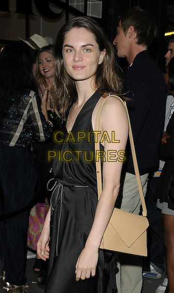 ANNOUK LEPERE .At the opening of the Acne London Studio, Dover Street, London, England, UK, July 15th 2010..half length black dress sleeveless beige bag .CAP/CAN.©Can Nguyen/Capital Pictures.
