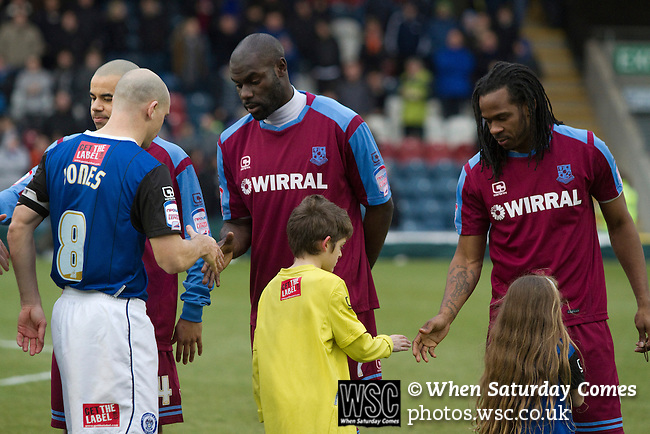 Rochdale 3 Tranmere Rovers 1, 01/01/2011. Spotland, League One. Tranmere Rovers Enoch Showunmi and Ian Goodison shaking hands with mascots and opposing captain Gary Jones on to the pitch at Spotland Stadium, before the team's Npower League 1 fixture away to Rochdale. It was the first league fixture between the teams since March 1989. Rochdale won this latest encounter by three goals to two watched by a crowd of 5,500. Photo by Colin McPherson.