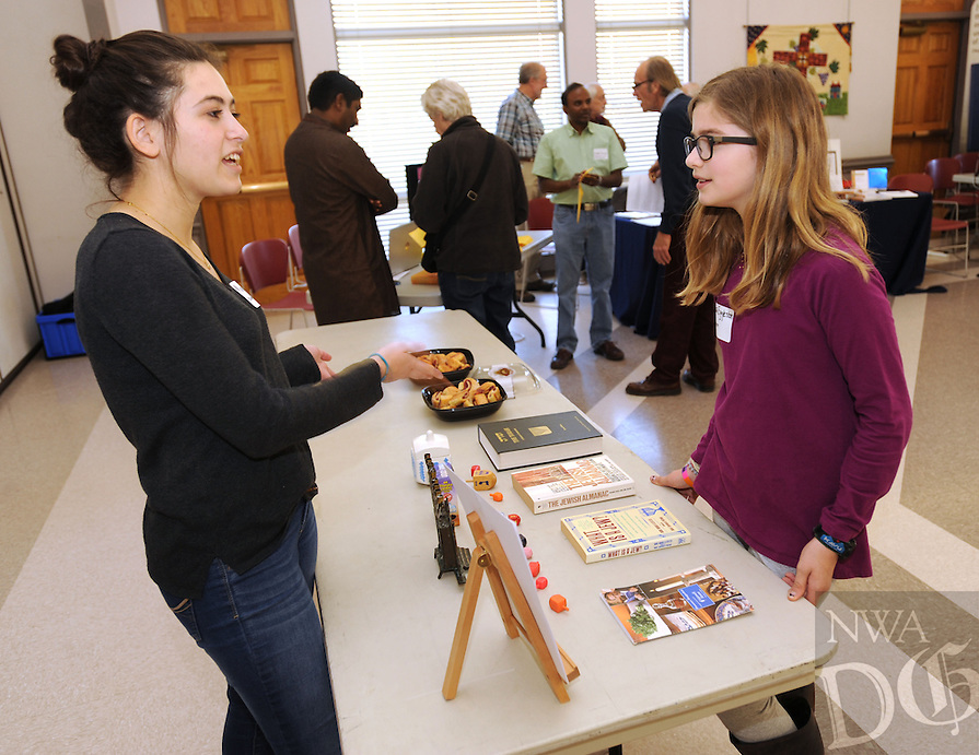 NWA Democrat-Gazette/ANDY SHUPE<br /> Maya Ungar (left), 17, a senior at Fayetteville High School and founding member of the school's COEXIST Club, speaks Saturday, March 19, 2016, with Fiona Eggleston, 11, of Fayetteville about the Jewish faith during Interfaith Harmony Day at St. Paul's Episcopal Church in Fayetteville. Representatives from many local faiths shared information about their faiths and answered questions for visitors.