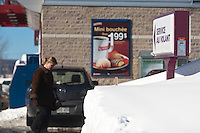 "A Dunkin' Donuts ""service au Volant"" (Drive-through) sign is seen on the Rue de l'Aeoroport Street restaurant in Quebec City February 24, 2009. Now owned by Alimentation Couche-Tard in the province of Quebec, Dunkin' Donuts is an international donut and coffee retailer."