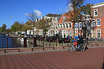 Woman and child biking across canal on way to train station, Haarlem, Netherlands