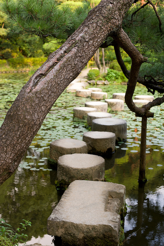 A trained pine bends over the stepping stones that make up the famous Garyukyo Bridge at Kyoto's Heian Shrine.
