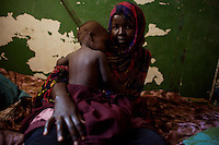 """Rahima Hammed, 22 years old, holds her baby  in the fomer Martini Hospital, her  new home since her family  was forced to leave their previous area due to recent fighting In  Somalia's war torn capital Mogadishu on Tuesday April 22nd 2008.///..Sporadic street fighting between Ethiopian .troops and Islamic fighters trying to bring down Somalia's shaky .government has killed 81 people on April 19 and 20, the head of a .local human rights group said Sunday. .""""The casualties ... were caused by Ethiopians using heavy artillery and .tank shells in residential areas of the war-torn capital. We condemn .this latest fighting,"""" said Sudan Ali Ahmed, chairman of Elman Human .Rights. Besides the 81 dead, 119 people had been wounded, he said. .Reports on Monday April 21 say Ethiopian troops have taken control of a mosque with a large .number of civilians inside following heavy fighting with insurgents. .The reports say a number of civilians were killed inside the mosque and others are being held by Ethiopians against .their will. .This apparent increase in the brutality of attacks may be caused partly by a .recent American decision to classify the Shabab (youth), the Islamic Courts .Union's former military wing, as a terrorist group. Battered by Ethiopian attacks .and by infighting between sub-clans engaged in the insurgency, Shabab .fighters now probably number fewer than 400. But America's decision to .demonise them has boosted jihadist commanders such as Aden Hashi Ayro, .strengthening his reputation for piety and anti-Americanism, which has itself .been boosted by recent missile attacks that have accidentally killed civilians...Philippe Lazzarini, head of the UN Office for the Coordination of Humanitarian Affai .rs (OCHA) Somalia, said on Monday April 21st that the combination of a severe drought, civil insecurity and h .yperinflation was pushing the country to the brink. If the situation were happening a .nywhere else """"it would have triggered outrage"""". .Lazzarini said Somal"""