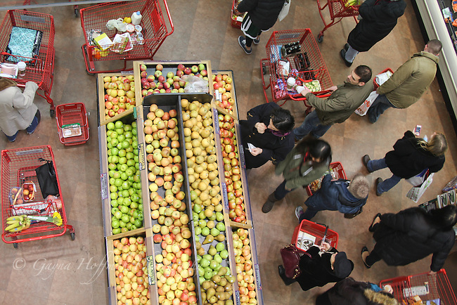 Shoppers in grocery store near fruit display.