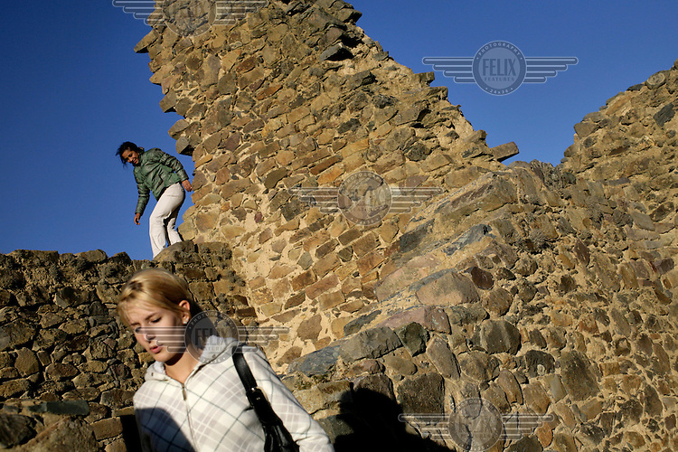 Tourists explore the ruins at Ollantaytambo that overlook the modern town known as the 'last living Incan town'. The town was built on top of Incan ruins and incorporates its stones and even some of the original stone doors.  ..