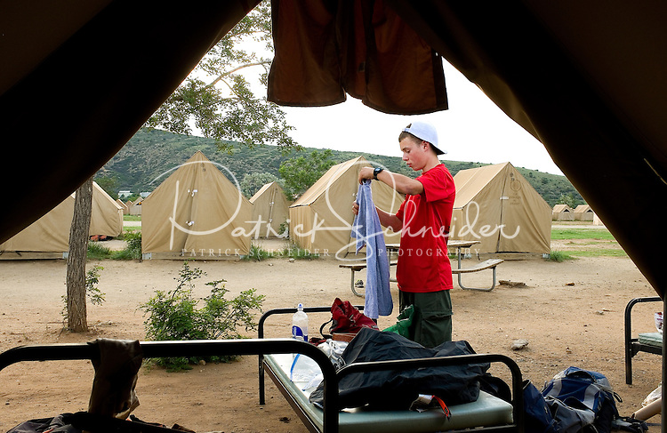 Photo story of Philmont Scout Ranch in Cimarron, New Mexico, taken during a Boy Scout Troop backpack trip in the summer of 2013. Photo is part of a comprehensive picture package which shows in-depth photography of a BSA Ventures crew on a trek. In this photo,  a Boy Scout VEnture crew member repacks his clothes  for the trip home after arriving back in base camp after completing his trek through the backcountry.<br /> Photo by travel photograph: PatrickschneiderPhoto.com