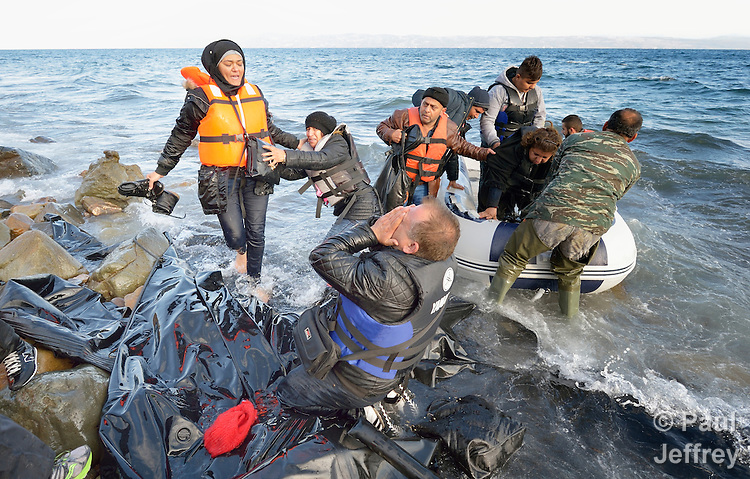 When he landed on the Greek island of Lesbos on October 30, 2015, Nabil Minas, a refugee from Syria, carried his children through the water and left them on the shore, then fell on his face and kissed the ground. A Christian, he crossed himself and covered his face with his hands, weeping with joy. The shore where he kneels is covered with the black rubber of deflated refugee boats.  Minas and his family came in the boat from Turkey, paying an exorbitant amount to traffickers who provided the transport.