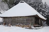 The cottage and surrounding woodland are carpeted in a thick layer of snow