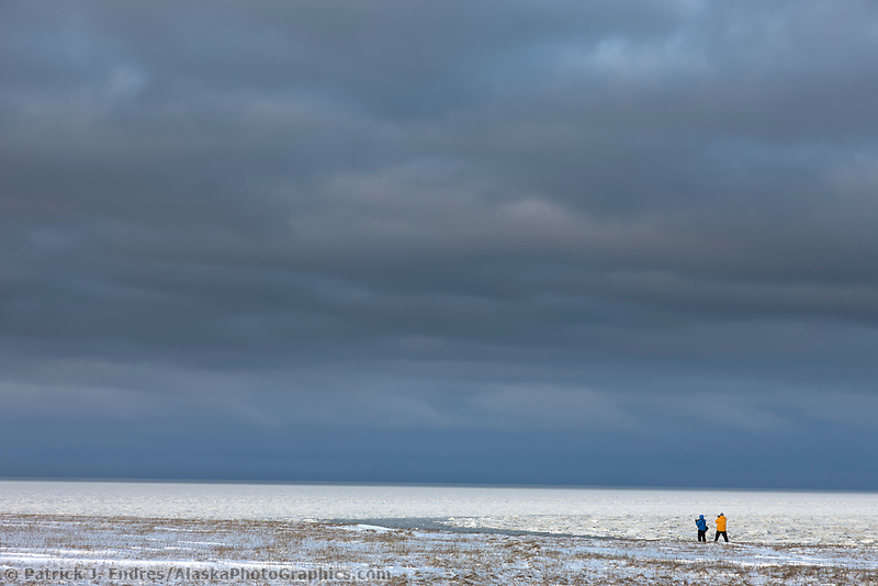 Photographers at the edge of Barter Island, overlooking freeze up on the Beaufort Sea, Alaska.