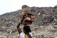 A woman carries bricks on her head at the Dhapa landfill in the west of Kolkata.<br /> <br /> To license this image, please contact the National Geographic Creative Collection:<br /> <br /> Image ID: 1925735 <br />  <br /> Email: natgeocreative@ngs.org<br /> <br /> Telephone: 202 857 7537 / Toll Free 800 434 2244<br /> <br /> National Geographic Creative<br /> 1145 17th St NW, Washington DC 20036