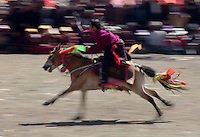 Khampa entertain the crowd in a rowdy horse race at the Litang Horse Festival - Kham, Sichuan Province, China, (Tibet)