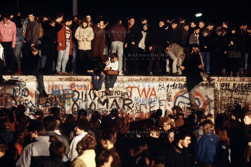 Berlino, 9 Novembre, 1989. Giovani Tedeschi durante le manifestazioni che hanno portato alla caduta del muro di Berlino. Packed perch<br /> Thousands of young East Berliners crowd atop the Berlin Wall near the Brandenburg Gate