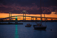 "The Green light on Goat island shines through a dramatic dark sunset fromt he ""The point"" looking at the Newport Pell Bridge"