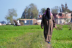 A woman walks across a field in the Egyptian village of Sakra.
