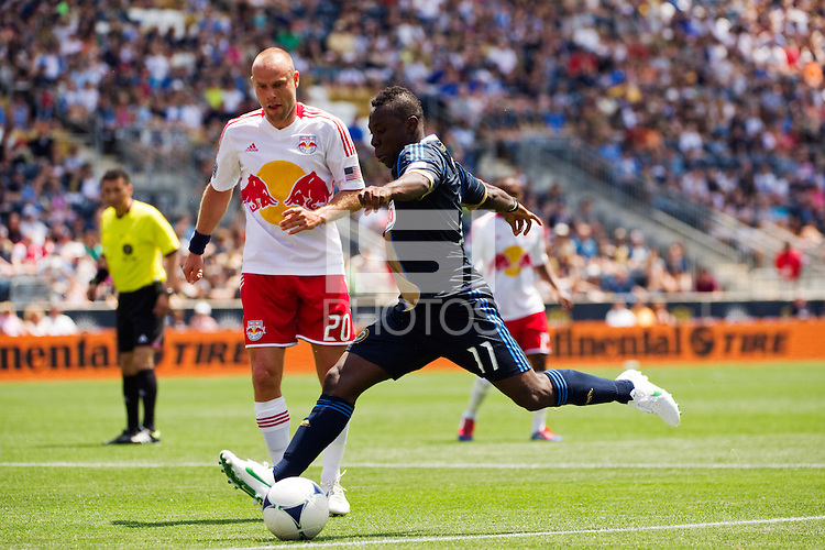 Freddy Adu (11) of the Philadelphia Union is defended by Joel Lindpere (20) of the New York Red Bulls. The New York Red Bulls defeated the Philadelphia Union  3-2 during a Major League Soccer (MLS) match at PPL Park in Chester, PA, on May 13, 2012.