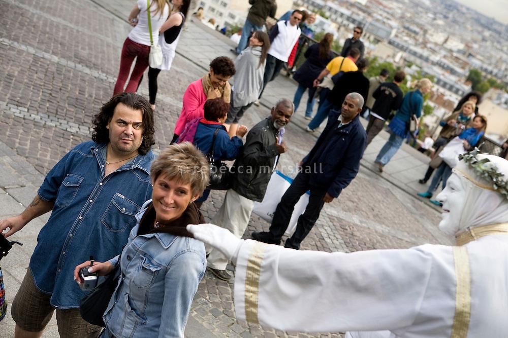 Tourists watch street performers at the Sacré-Coeur, Montmartre, Paris, France, 14 September 2009