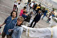 Tourists watch street performers at the Sacré-Coeur, Montmartre, Paris, France, 14 September 2009