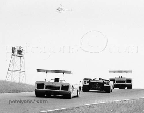 "McLaren M8Bs of Denny Hulme (5) and Bruce McLaren (in lead) sandwich Porsche 908 of Jo Siffert as they climb Watkins Glen's ""Graham Hill"" during 1969 Glen Can-Am race; PHOTO BY Pete Lyons 1969 / www.petelyons.com; scanned at 7200 ppi with USM setting at 20-1-1 on Plustek OpticFilm 7600 26Apr2013"