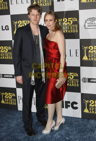 RENN HAWKEY & VERGA FARMIGA .25th Annual Film Independent Spirit Awards held At The Nokia LA Live, Los Angeles, California, USA,.March 5th, 2010 ..arrivals Indie Spirit full length red strapless dress silk satin cream clutch bag platform shoes heels black suit scarf  .CAP/ADM/KB.©Kevan Brooks/Admedia/Capital Pictures