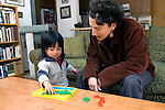 Berkeley CA Adoptive mother encouraging Guatemalan daughter, two-years-old to do puzzle  MR