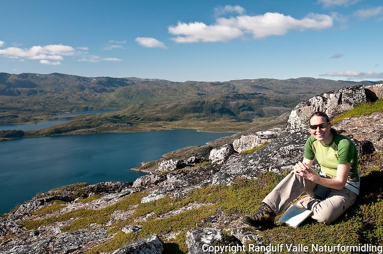 Utsikt fra Ramnesfjellet på Sørøya mot Øyfjorden. ---- Woman hiking on Sørøya a beautiful summer dag.