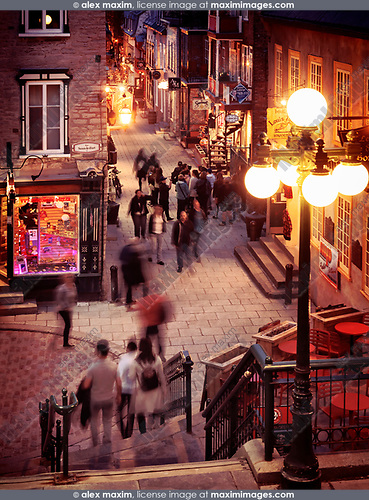 People walking at night on historic streets Rue du Petit Champlain and Rue Sous Le Fort of old Quebec City, view from above. Quebec, Canada. Ville de Québec.