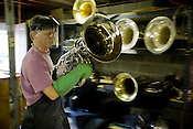 Tuba Exchange Repair Technician Mike Morse carries a tuba for cleaning in a ultrasonic cleaning tank.