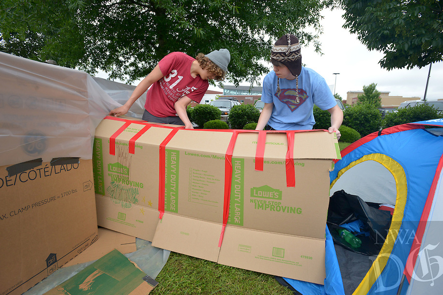 NWA Democrat-Gazette/BEN GOFF -- 05/30/15 Jai Thompson (left), 14, and Jack Burt, 15, assemble cardboard boxes to make their shelter during the Bentonville High School Chapter of Habitat for Humanity Sleep Out in front of the school in Bentonville on Saturday May 30, 2015. Students spent Saturday night in makeshift shelters to raise awareness about homelessness and collected nearly $2,000 in donations for Habitat for Humanity of Benton County, according to Joe Blair, the club's faculty sponsor.
