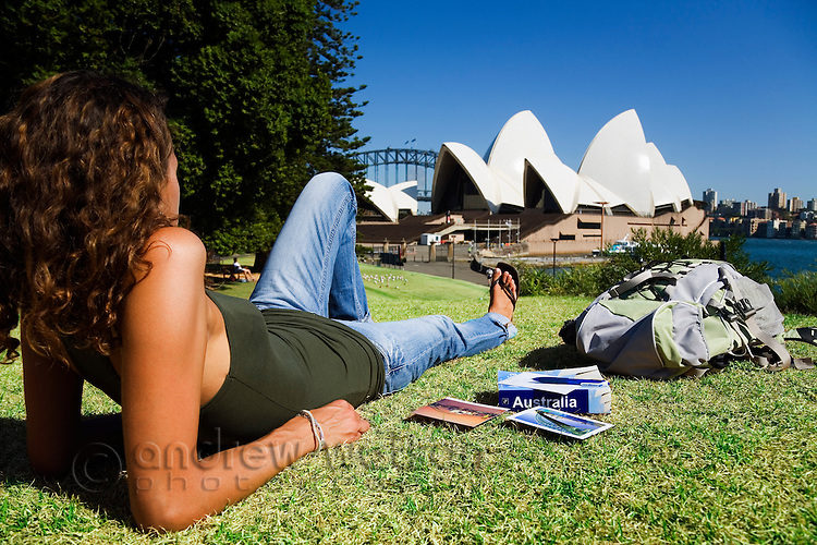 A tourist relaxes on the grass overlooking the Sydney Opera House.  Sydney, New South Wales, AUSTRALIA.