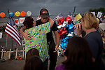 Amber Jaramillo, left, hugs an unidentified firefighter at a makeshift memorial that has formed outside Fire Station 7 in Prescott, Arizona, July 2, 2013, the home of the 19 Granite Mountain Hotshots who perished in the Yarnell Fire Sunday.
