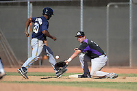 Colorado Rockies first baseman Kyle Parker (3) takes a throw as D'Vontrey Robinson (20) gets back to the bag during an instructional league game against the Milwaukee Brewers on October 1, 2013 at Maryvale Baseball Park Training Complex in Phoenix, Arizona.  (Mike Janes/Four Seam Images)
