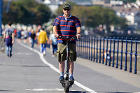 Pictured: A man rides his scooter on the beachfront during the sunny weather at Mumbles, near Swansea, Wales, UK. Thursday 19 September 2019