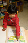 Preschool Headstart New York City 4 year old books and reading boy pointing at illustration in large picture book vertical