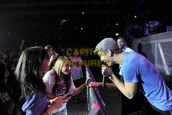 THE WANTED - Tom Parker.Performing live at the O2 Arena, London, England..March 17th, 2011.band group stage concert live gig performance music half length black trousers blue t-shirt harem side flat cap hat grey gray profile fan girl crowd fans girls singing audience .CAP/MAR.© Martin Harris/Capital Pictures.