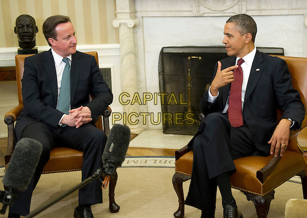 Prime Minister David Cameron of Great Britain and United States President Barack Obama meet in the Oval Office the White House in Washington, D.C. on Wednesday, March 14, 2012 following the Official Arrival Ceremony in Cameron's honor.  .full length black suit sitting side profile  hand.CAP/ADM/RS.©Ron Sachs/Pool/CNP/AdMedia/Capital Pictures.