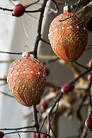 Close up of Christmas baubles hanging on branches of rose hip