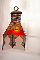 Detail of an ornate beaten metal lantern inlaid with red glass