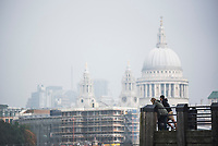 Couple on a pier overlooking St Paul's Cathedral on the banks of the River Thames, South Bank, London, England