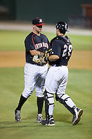 Kannapolis Intimidators relief pitcher Matt Cooper (32) shakes hands with catcher Ryan Plourde (28) after closing out the game against the Greensboro Grasshoppers at CMC-Northeast Stadium on June 11, 2015 in Kannapolis, North Carolina.  The Intimidators defeated the Grasshoppers 7-6.  (Brian Westerholt/Four Seam Images)