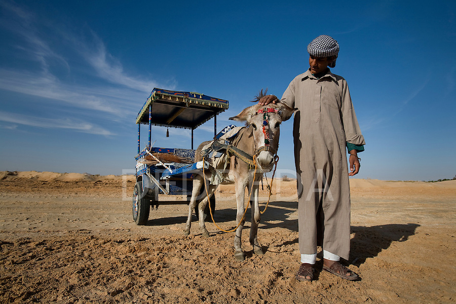 A local Siwan young man dressed in traditional clothing with his donkey and cart in the desert outside Siwa Town of the Siwa Oasis, Egypt.