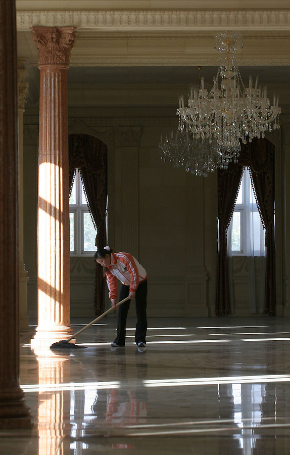 Beijing, China - October 21, 2005 - A worker cleans the floor at the Zhang Lafitte Chateau Hotel Chateau Zhang Laffitte is no ordinary imitation. It is the oriental twin of Château Maisons-Laffitte, the French architect François Mansart's 1650 landmark on the Seine. Its symmetrical facade and soaring slate roof were crafted using the historic blueprints, 10,000 photographs and the same white Chantilly stone. Yet its Chinese proprietor, a Beijing real estate developer named Zhang Yuchen, wanted more. He added a manicured sculpture garden and two wings, copying the palace at Fontainebleau. He even dug a deep, broad moat, though uniformed guards and a spiked fence also defend the castle. 'It cost me $50 million,' Mr. Zhang said. 'But that's because we made so many improvements compared with the original.' Photo by Natalie Behring