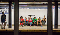 Subway riders wait for a train at the Delancey Street station on the New York subway on Saturday, May 17, 2014. (© Richard B. Levine)