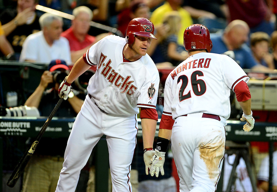 Apr. 17, 2012; Phoenix, AZ, USA; Arizona Diamondbacks catcher (26) Miguel Montero is congratulated by first baseman Lyle Overbay after scoring in the first inning against the Pittsburgh Pirates at Chase Field.Mandatory Credit: Mark J. Rebilas-