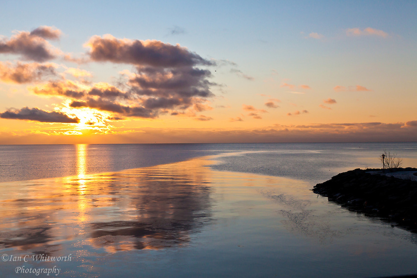A sunrise is reflected in the water of Lake Ontario at dawn in Toronto