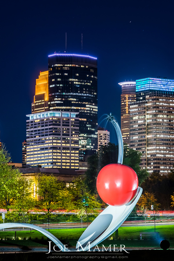 Spoonbridge and Cherry sculpture in front of Minneapolis skyline at nightt. Designed by Claes Oldenburg and his wife, Coosje van Bruggen. The complex fabrication of the 5,800 pound spoon and 1,200 pound cherry was carried out at two shipbuilding yards in New England. The sculpture has become a beloved icon in the Garden, whether glazed with snow in the Minnesota winters or gleaming in the warmer months, with water flowing over the surface of the cherry and a fine mist rising from its stem