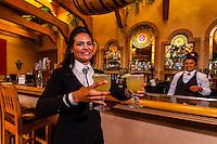 A waitress carrying margaritas in the bar of the El Pinto Restaurant and Cantina, Albuquerque, New Mexico USA
