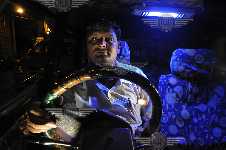 A taxi driver at the wheel of his cab is illuminated by a blue fluorescent light.
